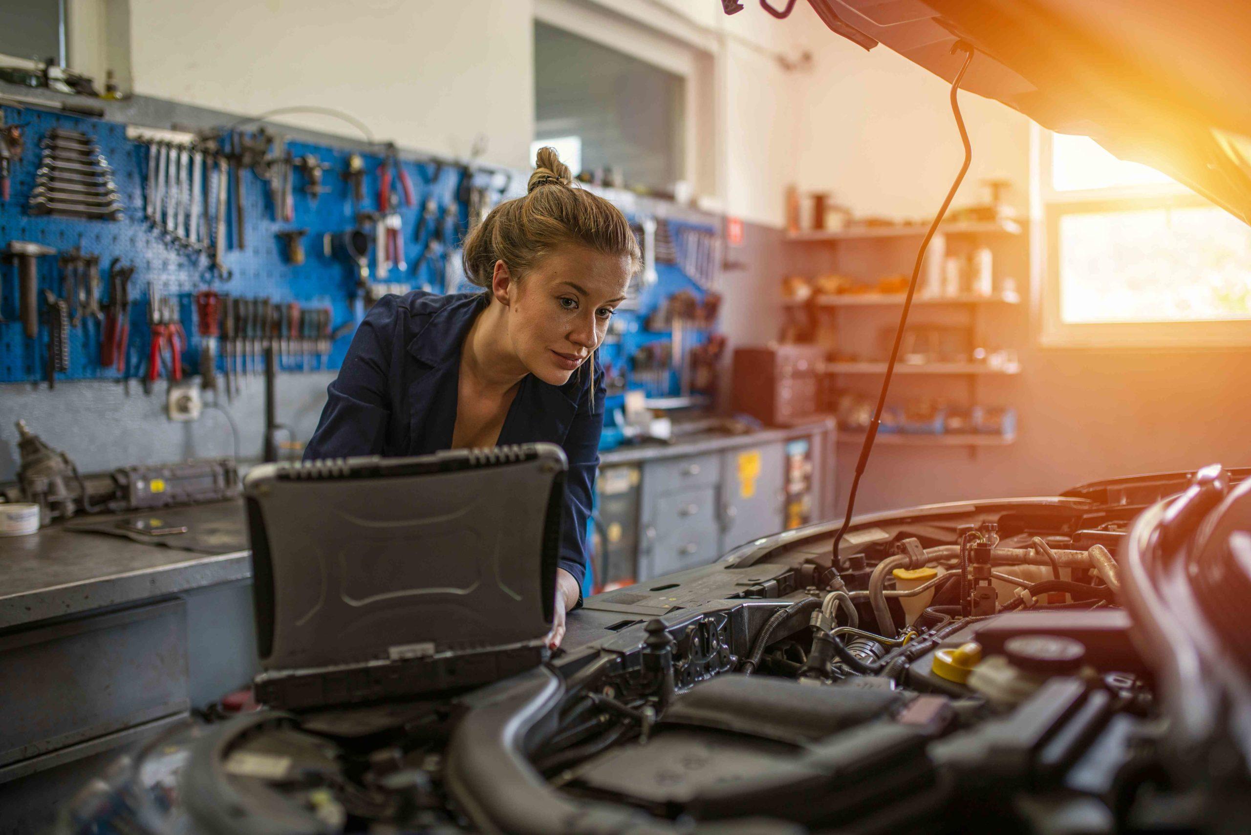 auto repair technician working on laptop in garahe