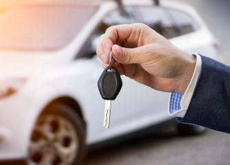 Male,Holding,Car,Keys,With,Car,On,Background